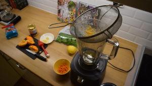 En mixer på ett bord. Frukter och skärbräda på bordet.