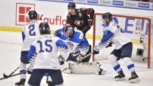 Ty Dellandrea och det finländska försvaret kämpar om pucken.