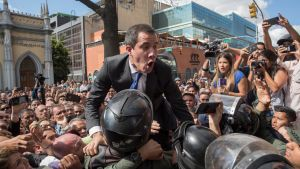 Den venezuelanska oppositionsledaren Juan Guaidó pressar sig förbi säkerhetsstyrkor den 7 januari 2020 för att kunna ta sig till parlamentet.
