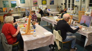 En mängd människor sitter vid bord och målar tavlor.
