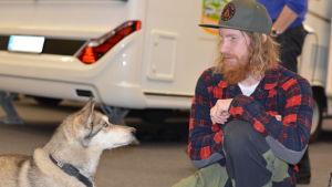 Niklas Hollsten tittar på sin hund på resemässa.