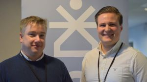 Två män bakom en plansch med logo. Rekryteringsmässa.