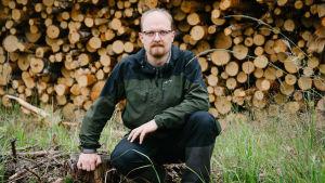 Man framför en enorm stapel fällda träd.