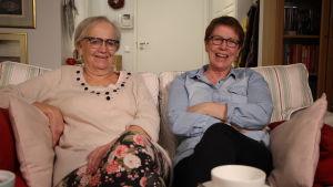 Iris ja Monna istuvat sohvalla.