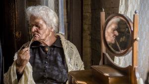 Helenes mor Olga röker pipa framför en spegel.