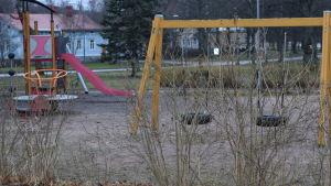 En lekpark tom på barn en höstlik, mulen och snöfri vinterdag i januari.
