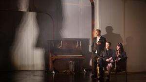 Tre människor i svart på en dunkel scen med vita väggar bredvid ett antikt piano i mörkt trä.