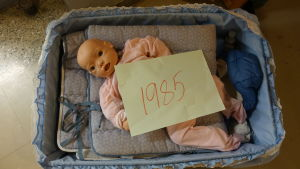 En leksaksdocka ligger i en liten säng.