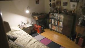 Ett ganska mörkt gästrum med säng, bokhylla, golvlampa som lyser och en kappsäck.