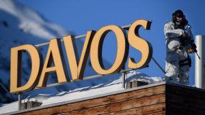 Beväpnad polis i vintermundering på snöklätt tak och skylt med ortsnamnet Davos.