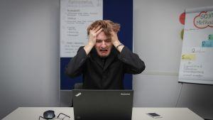 En man sitter framför en dator och river i sig i håret.