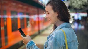 En ung kvinna ler och tittar på mobiltelefonen.
