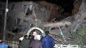 En grupp människor står och tittar på en ihoprasad byggnad i provinsen Elazığ.