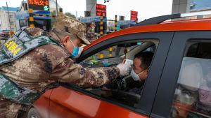 Sotilas mittaa autoilijan kuumetta.