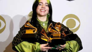 Billie Eilish ler brett med fyra Grammy-staytetter i famnen.