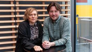 En ung kvinna och en ung man står vid ett bord.