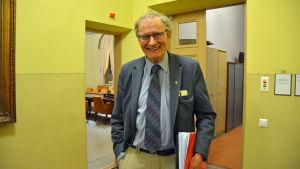 En man står i ett gult rum med en mapp under armen.