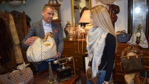 Nainen katsoo laukkuja antiikkiliikkeessä.