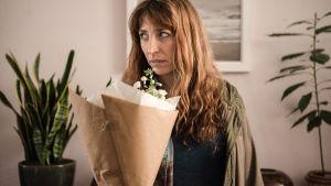 Nainen seisoo kukkapuska kädessään ja katsoo vasemmalle epäilevän oloisesti.