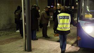 En polis med neongul väst står vid en buss och väntar på att en grupp asylsökande ska stiga på.