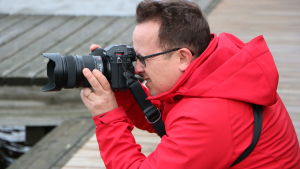 En man står på knä och fotograferar, med en brygga i bakgrunden.