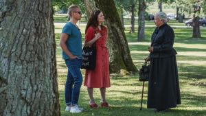 Man och kvinna i park tillsammans med äldre dam klädd i svart långklänning.