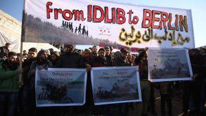 """Syrier samlas för att protestera i staden Harim i Idlib vid gränsen mot Syrien 2.1.2020. Texten """"Från Idlib till Berlin""""  hänvisar till flyktingarnas vädjan om ett öppnande av gränsen."""