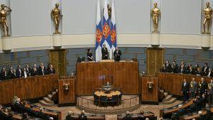 Högtidlig invigning i riksdagssalen, med president och talmän framför Finlands flaggor