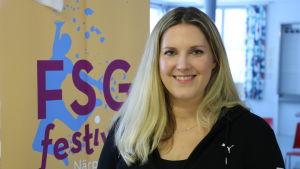 En ung kvinna med långt blont hår står intill en skylt med texten FSG-festival Närpes 2020.