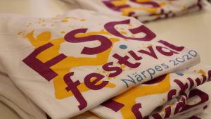 En hög med t-skjortor ligger på ett bord. Texten FSG-festival Närpes 2020 har tryckts på skjortorna.