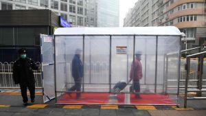 Människor promenerar genom en desinfektionstunnel i Peking 13.2.2020