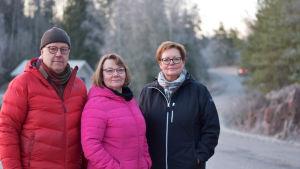 Tre personer står vid en väg.