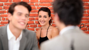En kvinna sitter framför en tegelstensvägg och ler mot två män som pratar sinsemellan.