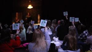 Yleisöä KPK-kyltit kädessä