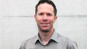 En man i grå skjorta står framför en grå vägg.