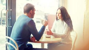 Ett par dricker kaffe på ett café.