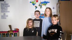 Fyra barn i ett klassrum.
