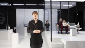 En skådespelare står på en vit scen. I bakgrunden glasväggar och två skådisar som sitter på en soffa.