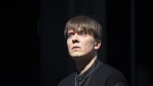 Närbild av skådespelaren Eero Riitala mot en svart bakgrund.