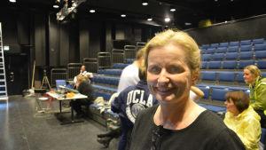 Marina Bergman, en dam med ljust hår och svart skjorta, står i en teatersalong.