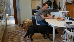 Svante Andström vid köksbordet tillsammans med hunden Bamse.