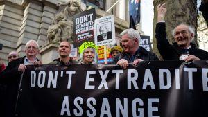 """""""Utlämna inte Assange"""" och """"journalistik är inget brott"""" står det på banderollen i London 22.2.2020"""