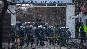 Grekisk kravallpolis stoppar migranterna som samlats vid gränsposteringen Pazarkule på den turkiska sidan.