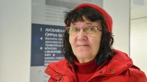 Närbild på en leende kvinna i röd jacka och röd mössa.