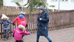 En vuxen kvinna och några barn på en skolgård, iklädda vinterkläder.