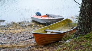 En motorbåt och en roddbåt ligger uppdragna på en strand.
