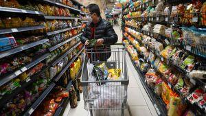 Kinesisk man med shoppingkärra i en  butik 12.3.2020