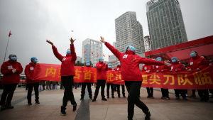 Vårdpersonal firar att antalet Covid-19-patienter minskat och ett temporärt sjukhus har stängts  i Wuhan, Hubei i Kina 9.3.2020.