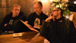 Tre män som pratar med varandra medan de ser på en LP-skiva.
