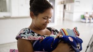 Kvinna tittar ner på sin bebis som hon har i famnen.
